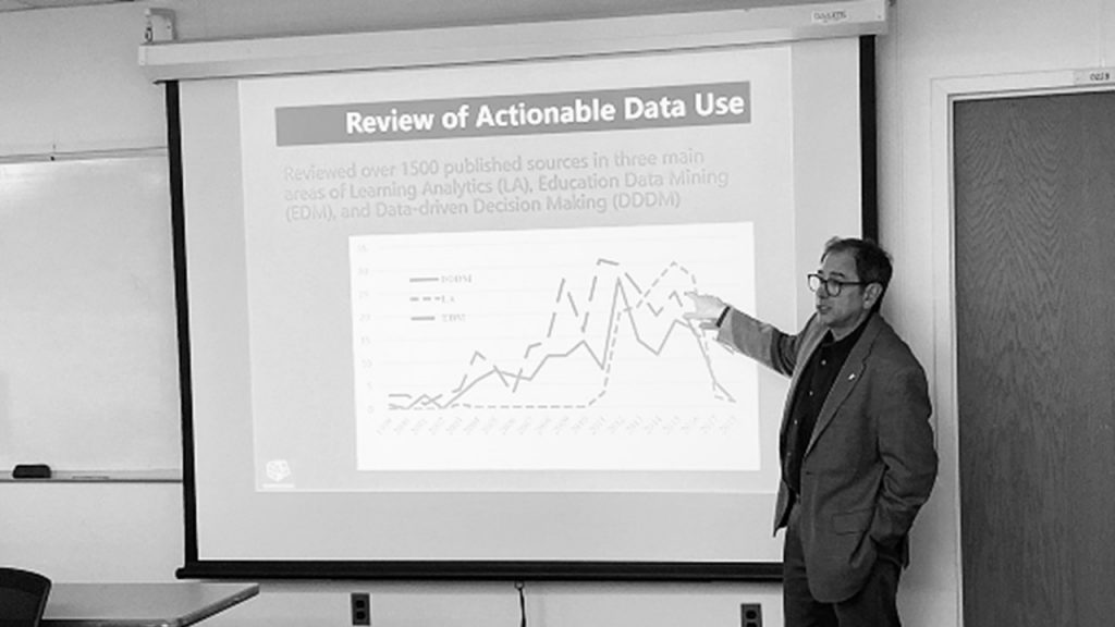 "Black and white photo of man in front of a projected screen of a graph titled ""Review of Actionable Data Use"""